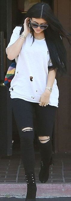 Who made  Kendall Jenner's print backpack, black boots, gold jewelry, and gray sunglasses?