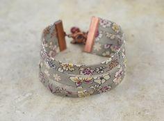 """Bracelet manchette composé de trois rangs de biais en liberty fleurs blanches et prunes sur fond beige. Bracelet terminé par une breloque """"oiseau"""" en métal cuivré et une perle - 13087535"""