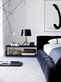 A Foscarini Lumiere table lamp sits on a large side table beside a B&B…