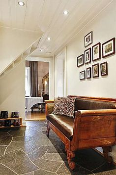 Entryway, white walls, paved floor, leather bench, good picture display