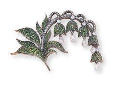 A TSAVORITE AND DIAMOND FLORAL BROOCH   Designed as a series of tsavorite lilies, each suspending a briolette-cut diamond, to the circular-cut diamond stems and tsavorite leaves