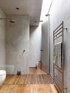 salle de bains moderne au charme industriel avec un mur en béton banché et revêtement de sol en bois
