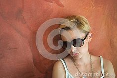 Portrait of a beautiful girl sitting at the wall. The girl has closed eyes. Nice contrast between pale skin and shades of red of the wall.