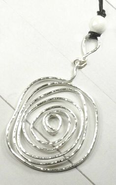 Silver spiral necklace - Large spiral pendant - Hammered metal necklace - Festival necklace - Statement jewelry - Wire jewelry  I made this large spiral from heavy gauge silver colored Artistic Wire. The spiral was hammered on a steel bench block to give it a nice texture, and also a little sparkle. The reverse side has less texture, so you can wear it either way, depending on your mood and outfit. A frosted white ceramic bead accents the top of the bail.  This is a great piece to wear to a…