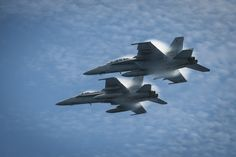 PACIFIC OCEAN (Aug. 24, 2014) An F/A-18C Hornet from the Stingers of Strike Fighter Squadron (VFA) 113 and an F/A-18E Super Hornet from the Fighting Redcocks of Strike Fighter Squadron (VFA) 22 fly in formation over the flight deck of the aircraft carrier USS Carl Vinson (CVN 70). Carl Vinson is underway off the coast of Southern California conducting Carrier Qualifications as part of the ship's Western Pacific Deployment 2014. (U.S. Navy photo by Mass Comm Spec 2nd Class George M.Bell)