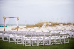 Beach Wedding Arch decorated with White Hydrangea, White Garden Roses, and Dusty Miller at the corners and tiebacks and White Hydrangea and Baby's Breath Aisle Markers | By Andrea Layne Floral Design (www.andrealaynefloraldesign.com) | Photo Credit: Aaron Lockwood Photography