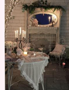 lovely shabby chic / vintage / cottage romance decor. candle light, Christmas lights, gauzy table fabric, ruffles, white wrought iron, oval mirror, white mantel, greenery - every part contributes. this is lovely!