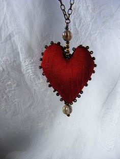 Ruby is so called because of the ruby red silk heart that is the focal point of my new textile necklace. All handmade, this is an original 7thMagpie design. The chain and findings are copper and brass and the richness of these metals complement the dark red silk heart and blue/bronze beads. The length of this stunning piece is: 48cm but may be shortened if you wish it shorter. The little heart is 4.5x4cm. There is no catch to this necklace, it just slips over your head! Should you lke th...