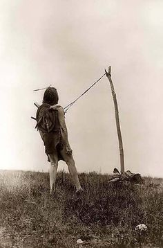Piercing Ritual. Which a man is suspended by leather straps attached to sticks in his chest. He is tethered to a pole that is secured by rocks. This is all part of the ritual of the Sun Dance. This is an original photo