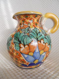 """...a Talavera polychrome pottery pitcher, exquisitely detailed and hand crafted in Puebla, Mexico. It is signed by the artist. It measures about 4 inches in height, and is exquisitely detailed in its pattern and design. It has a circular applied handle. The glaze is thick and has a nice tactile quality to it."""