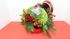 Festive Holiday arrangement in a Christmas ornament type vase with mini green hydrangea, red roses, red berries with Christmas greens. #florist #flowers #flowershop #centerpiece #florals #flowerarrangement #floralarrangement #roses #carnations #pinecones #berries #candles #holidays #christmas #greens #flowersoftheday #flowerlover #flowerlovers #flowerpower #blooms #hydrangea #redroses #hydrangeas