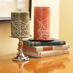 Spiderweb Candles - Basic dollar store candles and a pencil are all you need to create this Halloween craft. Simply use the pencil to draw a spiderweb design into each pillar candle. Once you've completed your design, pour a little bit of rubbing alcohol onto a paper towel and dab the excess wax off the candle surface.