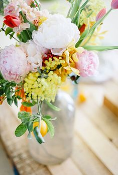 Brides.com: . Orange accents are a playful part of this rustic peony centerpiece.