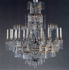 A Fine Baltic Neoclassical Gilt-Metal & Cut-Glass, 16-Light Chandelier. Late 18th Century.  The upper corona with interlacing strap work suspending cut-glass drops and prisms, and fitted with eight curved gilt-metal supports continuing to the lower ring with concave & rectangular gilt-metal panels fitted with eight pairs of lights; the gilt-metal supports linked by cut-glass beaded chains. The whole suspending beads and cut-glass prisms. 46 x 46 Inches. Approximate Value: $120,000.