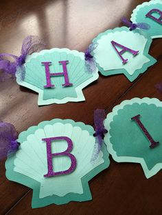 Made to order This banner was handmade with quality cardstock. The letters were cut from glittered cardstock and mounted with foam. Tied together using purple glitter tulle. Each seashell measures 5 by 6 Great addition to any Mermaid party! Please include your childs age during checkout. Message me for matching name banner.
