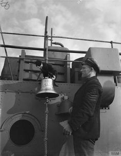 """HMS KELVIN'S SHIPS MASCOT. SEPTEMBER 1940, ON BOARD THE DESTROYER IN HARBOUR. """"Splinters"""" the ships cat is well known for his antics and is found in many unlikely places. Here he is on the ship's bell."""