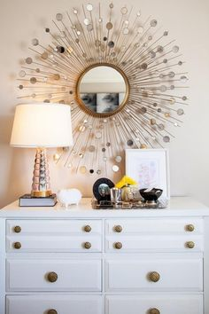 A simple dresser plus lamp plus mirror combination dazzles like a Broadway show thanks to golden drawer pulls and a sunburst mirror. A tray neatly corrals photos, jewelry and other accessories.