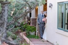 Bride and Father peeking around the corner as they head down the aisle. Lionscrest Mountain Private Event Venue floral cedar tree path. Lyons, Colorado.