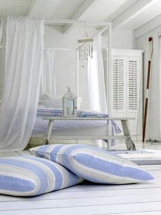 love this room, the sheers, white bed frame, louvered doors on armoir, blue and white cushions, shell wind chime, oar, planks, layered blue and white scatter rugs