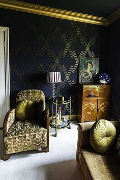 Stunning glamorous living room. Black and gold wallpaper. Green accessories and vintage furniture and mini drinks trolley.