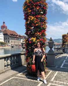 CHLOE.ROXANE - Instagram : Discovering Lucerne, Switzerland in an outfit with a flower crop top, a black skirt, white sneakers and a small red backpack.