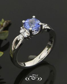 Custom 950 platinum mounting holding a 4-prong set round cut blue sapphire.