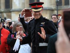 The 33-year-old royal smiles and waves as onlookers take pictures of him on their camera phones this morning