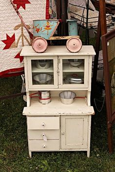 I have this same adorable childs hoosier cabinet, filled with vintage children's kitchen things. Love it!