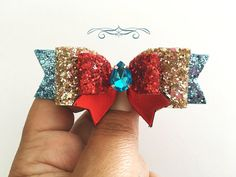 Disney Princess Elena of Avalor Red Pink and Gold Hair Bow  This piece is inspired by the new Disney Princess Eleanor of Avalor. If you would like colors substituted, please message me. Approx. 3 1/2 wide  Layers of Beautiful hand cut chunky glitter fabric hand lined with felt for comfort and design, topped with a rhinestone Gem Center.   Please choose from the wide array of options of hardware for your choice.  All pieces are made to order so you receive a freshly made piece. No factories…