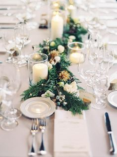 Lush and organic winter tablescape with green garlands sprinkled with flowers like roses and hellebore.