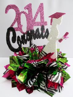 In the first picture we feature the table centerpiece with our custom horizontal 2014 and just the base which is comprised of zebra stripes tissue, lime green and fuchsia mylar puffs. In the second...