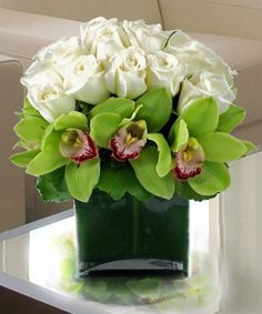 Two of our favorite flowers come together to create a wonderful arrangement. White roses and green cymbidium orchids in a trendy leaf lined vase. Types Of Flowers, All Flowers, Fresh Flowers, Pretty Flowers, Modern Flower Arrangements, Orchid Arrangements, Valentine Flower Arrangements, Deco Floral, Arte Floral
