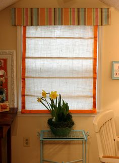 A roman shade in an unexpected fabric (burlap), plus a valence provides privacy and color.  The ribbon around the edge softens the roughness of the burlap.  Great for an apartment so you won't have neighbors peeking in.