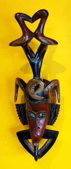 Guru masks originally from Ivory Coast, East Africa Hand carved out of ONE piece of wood. Extremely detailed art work. This noble mask is adorned with the horns of a ram and a bird leaning forward. Fo
