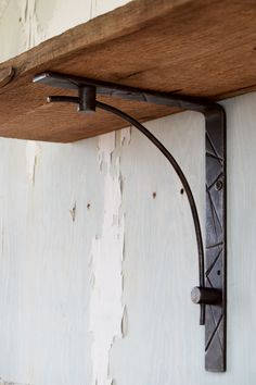 Hand-forged metal shelf bracket with blackened iron finish. Impressions are done…