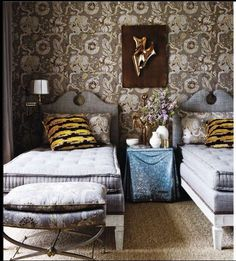 twin French mattresses, oversize wallpaper print, and unusual bedside table distinguish this room.