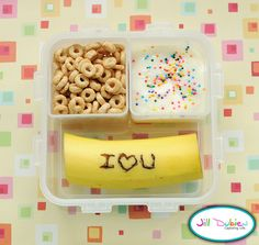 from meet the dubiens blog    Here's one for her morning nutrition break. A banana with a message. You can use a toothpick to write a message in your banana peel and it will darken so your child can read the message. Now Kirsten can't really read, but she knows I love you. She really loved it. A container of yogurt with sprinkles and a container of cheerios.