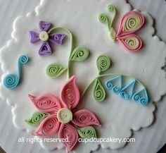 I took an excellent class from Dianne Gruenberg on the art of quilling.  Traditionally, quilling is done with thin strips of paper.  In this interpretation, I used thin strips of gumpaste in the place of paper on a basic fondant plaque (ugly cake cardboard in the background).  I can just imagine all of the possibilities on a cake!   ---------------------------------------- Cupid Cupcakery  Baked to order wedding and special event cakes and cupcakes.  Fairview Park, OH 330.606.2666…