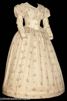 A very lovely original circa late 1830's lady's floral printed cream silk challis one piece gown. The bodice is lined and stayed, with a fan pleated front, piping at all the seams, with fashionable slender capped sleeves, a two part back with a blind hook and eye closure, a cartridge pleated waistband, and an unlined skirt with a deep turned and faced hem. New York State museum with a 1968 museum accession numbered tag still attached.