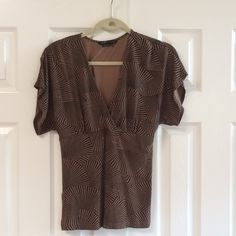 BCBGMAXAZRIA v-neck blouse The pattern on the top is like a black and brown fan design. Is 94% rayon 6% spandex.  The top is been gently washed and worn and has no rips or stains. BCBGMaxAzria Tops Blouses
