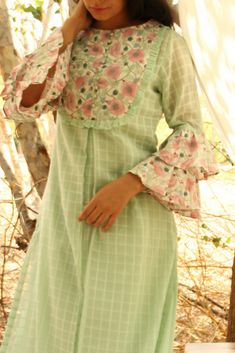Florid Frill - Retro Sleeve Tunic and Floral Pant SetFeatures a set of three - Mint green mull checks kurta with slip and floral pants, frills at the sleeves, front yoke. Kurti Sleeves Design, Kurta Neck Design, Sleeves Designs For Dresses, Dress Neck Designs, Printed Kurti Designs, Tunic Designs, Kurta Designs Women, Curvy Work Outfit, Cotton Tunics