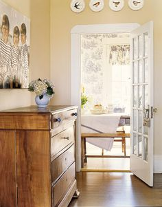 Pretty 15-light white French door opening into the dining room compliments the soft tan colored walls and light brown hardwood floors.