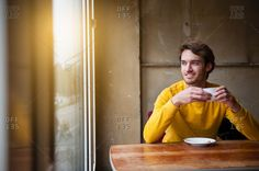 Young man sitting in cafe drinking coffee