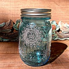 A new pint sized, blue glass, Ball Heritage mason jar adorned with silver mandalas. 5 handpainted silver mandalas wrap all sides of the glass,