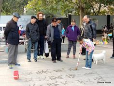 A crowd gathers to watch a young girl practice Di Shu calligraphy on the pavements of Xi'an, China Crowd, My Photos, Calligraphy, China, Watch, Lettering, Clock, Bracelet Watch, Clocks
