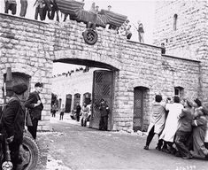 Survivors eagerly pull down the Nazi eagle over entrance to the Mauthausen concentration camp.