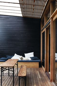 I like the wood painted black against the natural wood, the table and benches, and the built in seating that mirrors the wall and floor