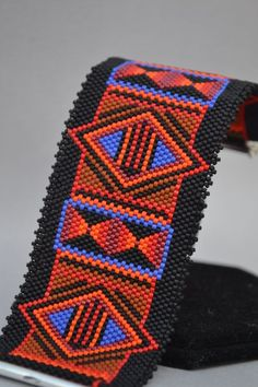 Geometric patterns and bold colors are what make this peyote bracelet stand out. The colors used are red, orange, blue, cranberry, sienna, and