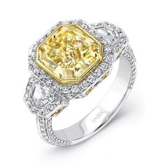 A warmly-tinged 3.24-carat radiant-cut fancy light yellow diamond takes center stage in this ravishing estate-inspired three-stone engagement ring from Uneek's Natureal Collection; fans of the vintage look will love the geometric halos surrounding the center and the sidestones, softened by the scroll motifs under the galleries; the knife-edge shank holds four rows of micropave diamonds