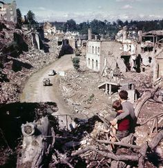 A view from a hilltop overlooking the road leading into St. Lo in July of 1944. Two French children in the foreground watch convoys and trucks of equipment go through their almost completely destroyed city en route to the front. AP Photo